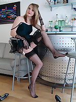 Leggy blonde posing in mini cocktail dress and black nylons