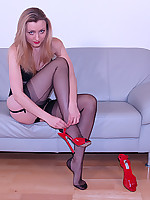 Blonde teasing with her long legs in black lingerie and seamed nylons