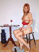 Bored secretary drinking wine and stripping in nude nylons